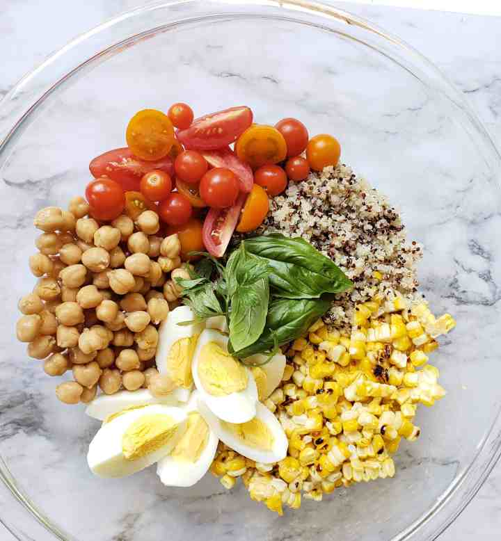 Quinoa, chick peas, Instant Pot cooked eggs, tomatoes, roasted corn, basil in mixing bowl not mixed together