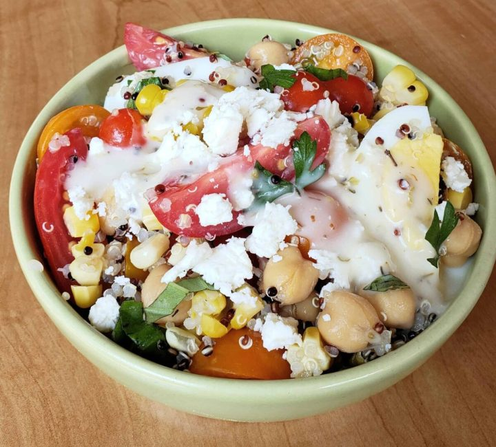Tri color quinoa salad with grape tomatoes boiled egg and chick peas in a green bowl on a red and white napkin with Greek dressing