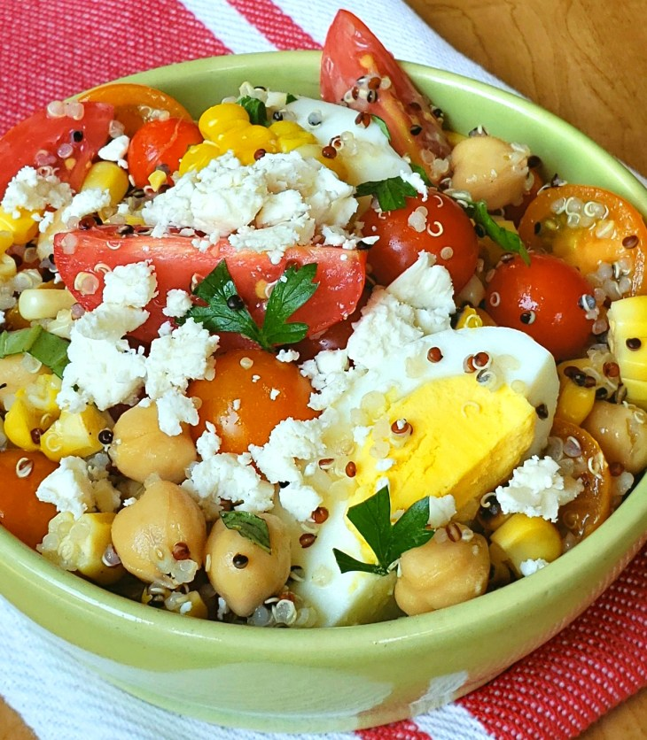 Tri color quinoa salad with grape tomatoes boiled egg and chick peas in a green bowl on a red and white napkin with feta