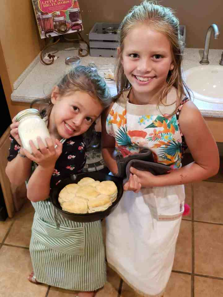 two girls holding cast iron skillet full of biscuits and a jar of homemade butter
