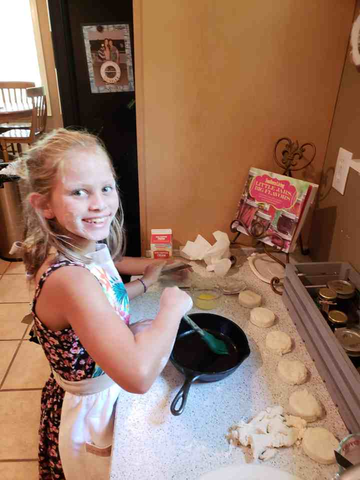 A girl brushing butter on the bottom of a cast iron skillet before placing biscuits in to bake.