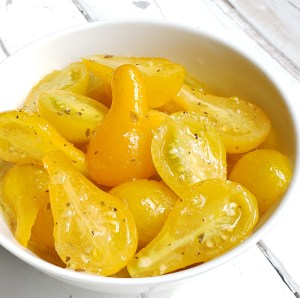 White bowl of Marinate Yellow Teardrop Tomatoes on white painted wood
