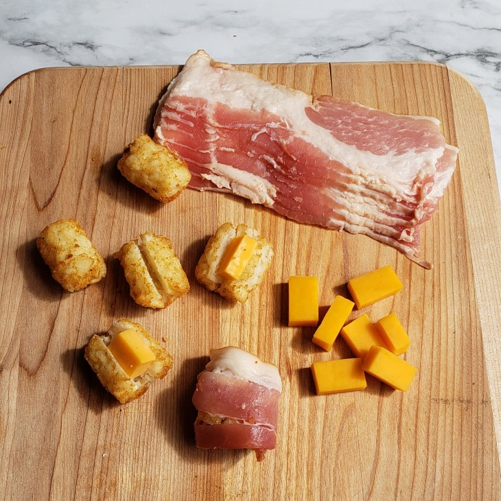 Tator tots, cheddar cheese, and bacon assembed on a cutting board to make bacon wrapped tator tots