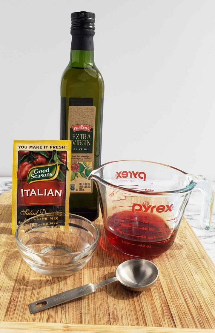 bottle of olive oil, measuring cup with blackberry vinegar, metal tablespoon, little glass bowl, package of dry Italian Salad dressing