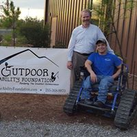 Scott Phillips and Grayson Phillips next to the Outdoor Ability Foundation banner. Grayson is in an Action Trackchair