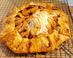 Apple galette with caramel drizzled on the melting ice cream. The shortcut apple pie is placed on a wire rack
