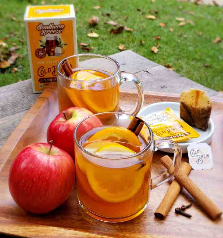 Sweet tea apple cider mugs on a wooden plate outside on a table with fallen leaves. Southern Breeze Sweet Tea bags on the table.