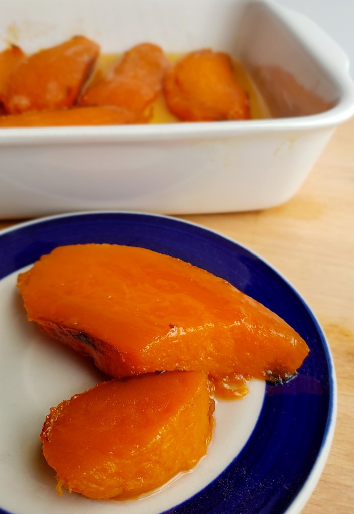Candied Roasted Sweet potato spooned onto a blue rimmed plate with remaining sweet potatoes in baking dish in background