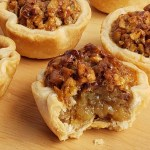 Mini pecan pie with bite taken out on wooden surface and additional tassies around it