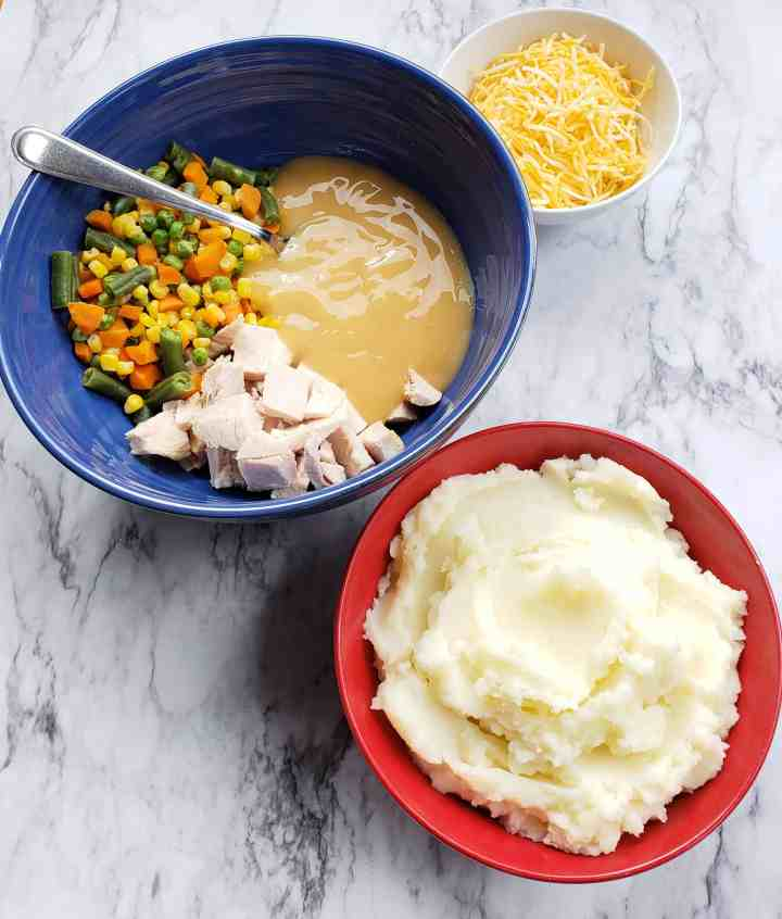 Blue bowl filled with mixed vegetables, chopped turkey, and gravy. Red bowl of mashed potatoes. small white bowl of shredded cheese.
