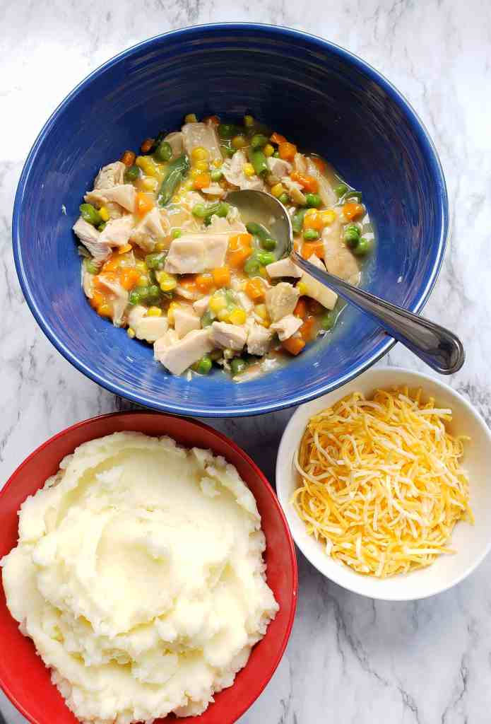 Chopped turkey, vegetables, and gravy in a blue bowl. Mashed potatoes in a red bowl. Shredded cheese in a small white bowl.