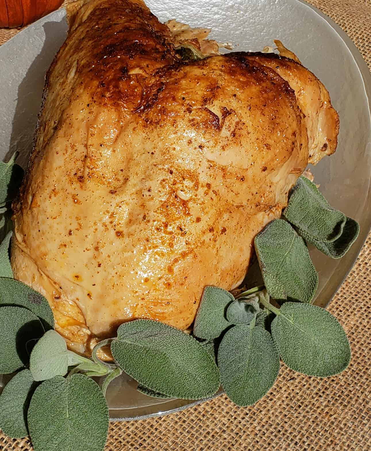 Turkey Breast cooked in Instant Pot on a glass platter with sage garnish