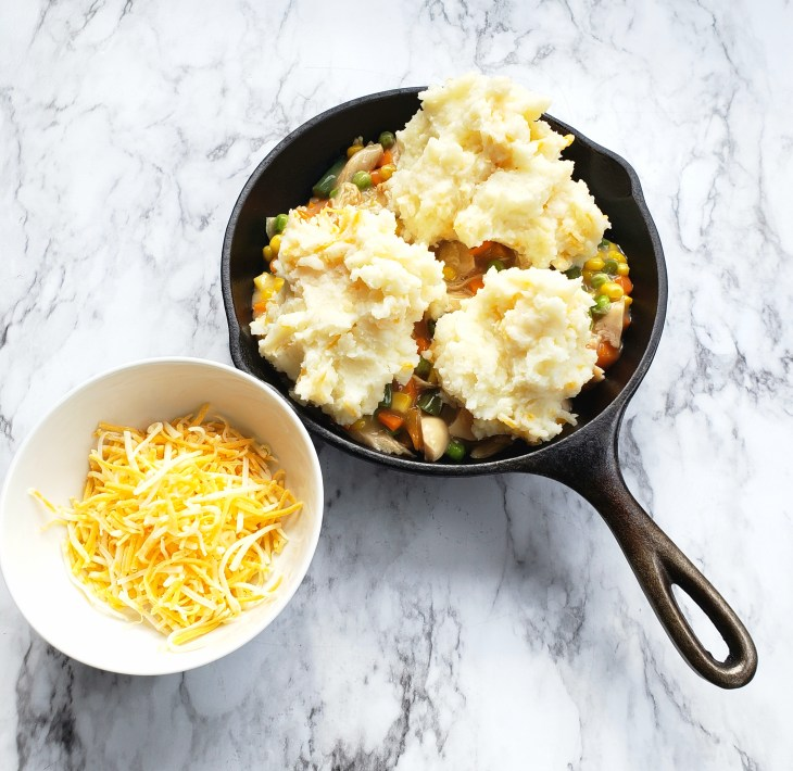 Vegetables and gravy and turkey in a cast iron skillet with mashed potatoes dolloped on top. Small white bowl of shredded cheese