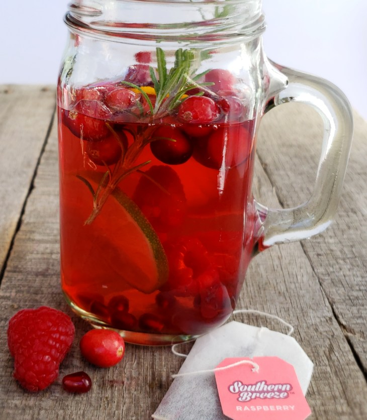 Sweet Tea Sangria Skinny Mocktail is your answer to a holiday drink without the alcohol! The tannins in tea mimic the tannins in red wine plus it is only 5 calories! Served in a mason jar with a handle on a wooden surface.