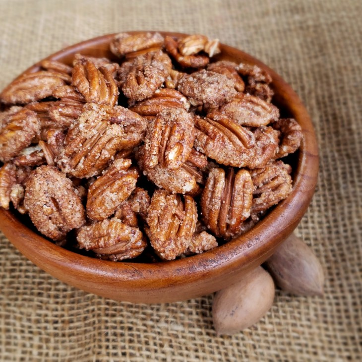 Cinnamon Sugar Pecans in a wooden bowl on burlap with 2 pecans in the shell