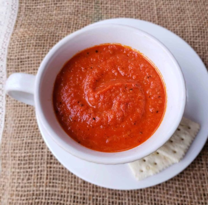Tomato and Bread Soup swirled in a white coffee cup on a saucer with saltine crackers on the side on burlap surface