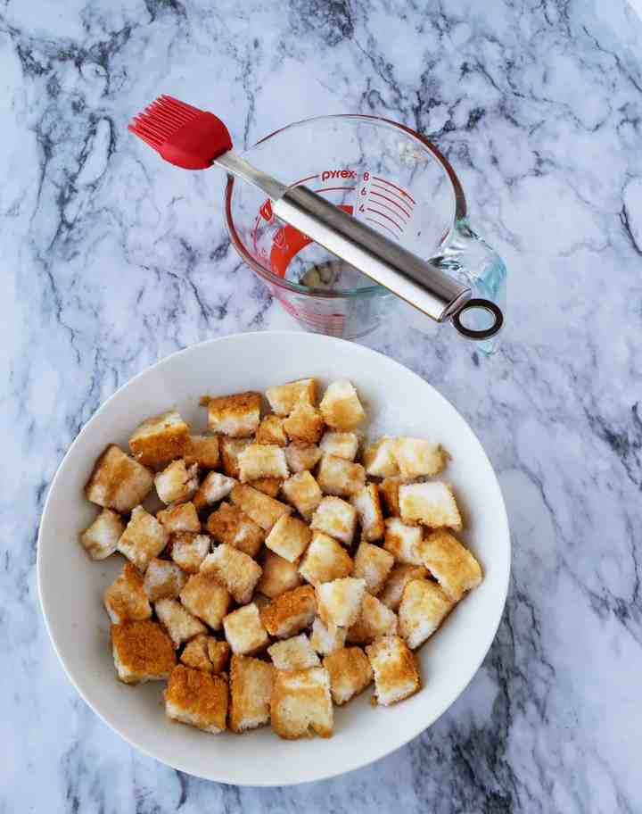 White bowl of angel food cake cubes soaked in sweet tea with pastry brush on measuring cup