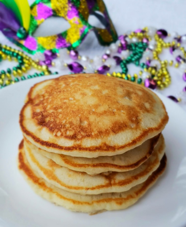 A stack of shortcut banana pancakes before drizzling icing and sprinkles on top. Mardi gras beads in back ground