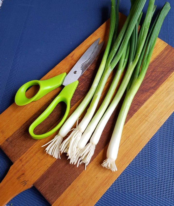 Green onions with Green scissors and wooden cutting board