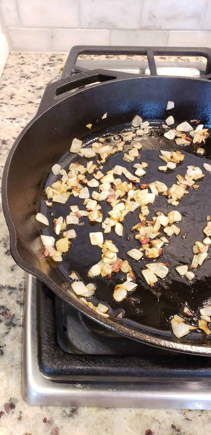 browned chopped onion in a cast iron skillet on a stovetop