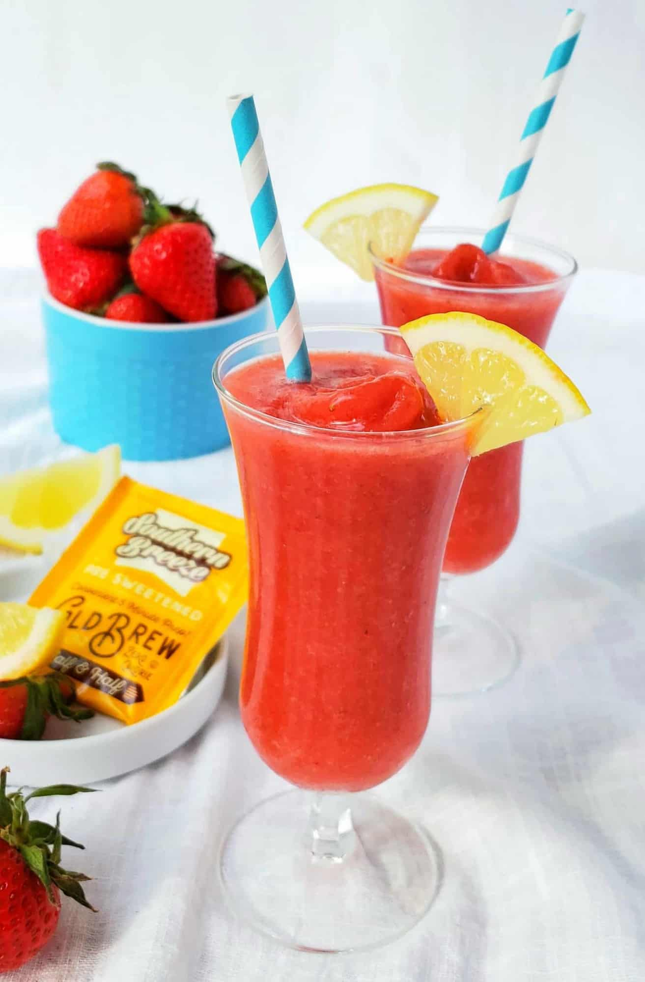 2 Ingredient and 2 Minutes to prepare Frozen Strawberry and Sweet Tea Lemonade is made with zero calorie sweet tea! Garnish with lemon slice and blue striped paper straw with Southern Breeze sweet tea individual tea bag on a white plate.