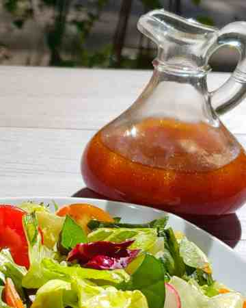 red salad dressing in a glass cruet next to a white plate of salad
