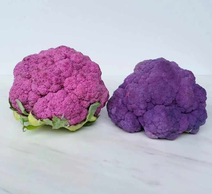 Raw and blanched heads of purple cauliflower side by side. Blanched is darker on the right side.
