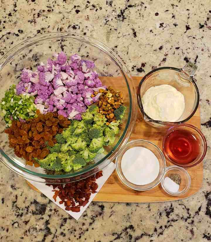 Broccoli Raisin and Purple Cauliflower Salad ingredients on a cutting board: red wine vinegar, Dukes mayonnaise, green onion, golden raisins, broccoli, purple cauliflower