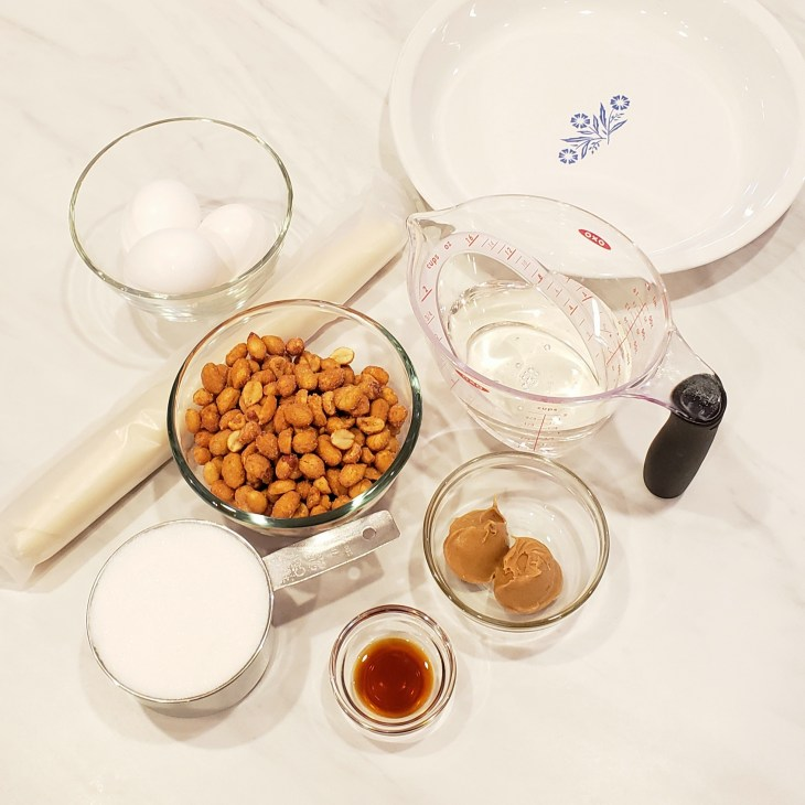 Ingredients for honey roasted peanut pie with white pyrex pie plate