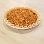 peanut pie filling with peanuts in fluted pie crust