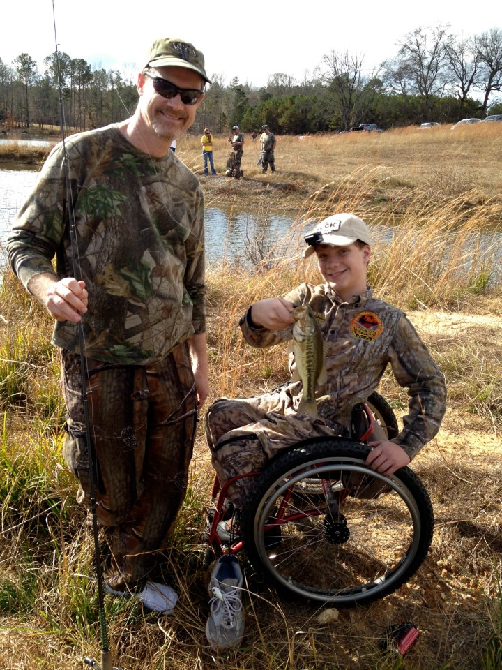 Scott and Grayson Phillips holding up an albino fish boy in wheelchair fishing