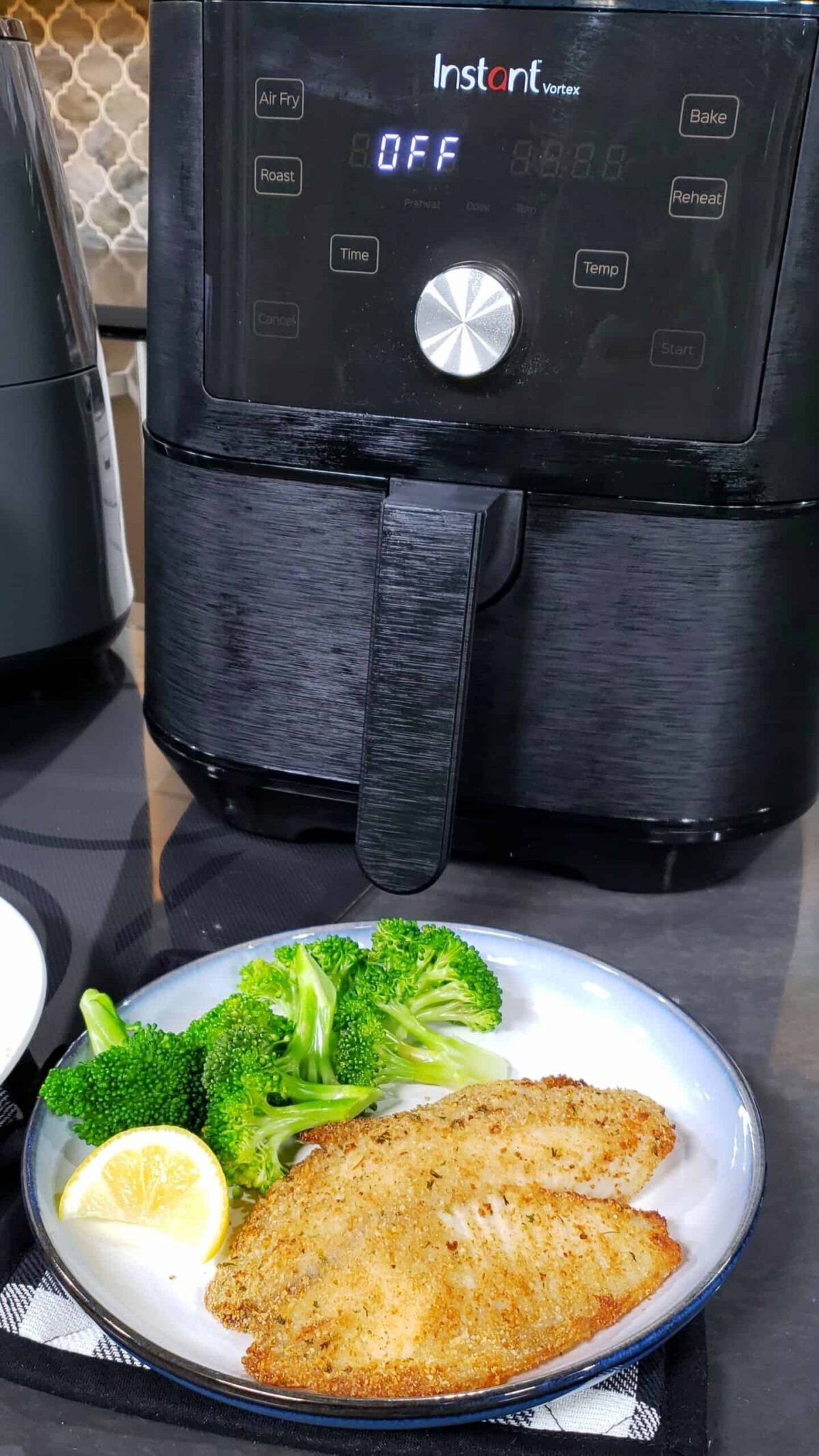 breaded tilapia on blue and white plate with broccoli and lemon with air fryer
