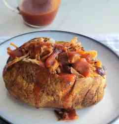 Baked potato stuffed with meat covered in sauce on a white plate. A clear tiny pitcher of bbq sauce in background