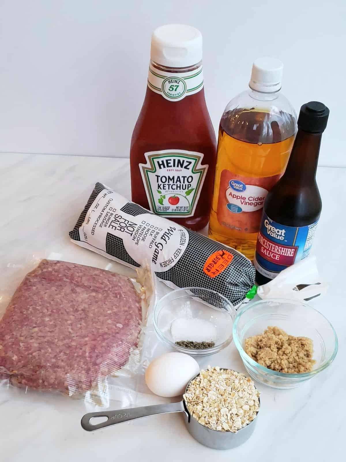 Ingredients on marble surface: ketchup, one pound ground meat, egg, brown sugar, vinegar, worcestershire sauce, venison