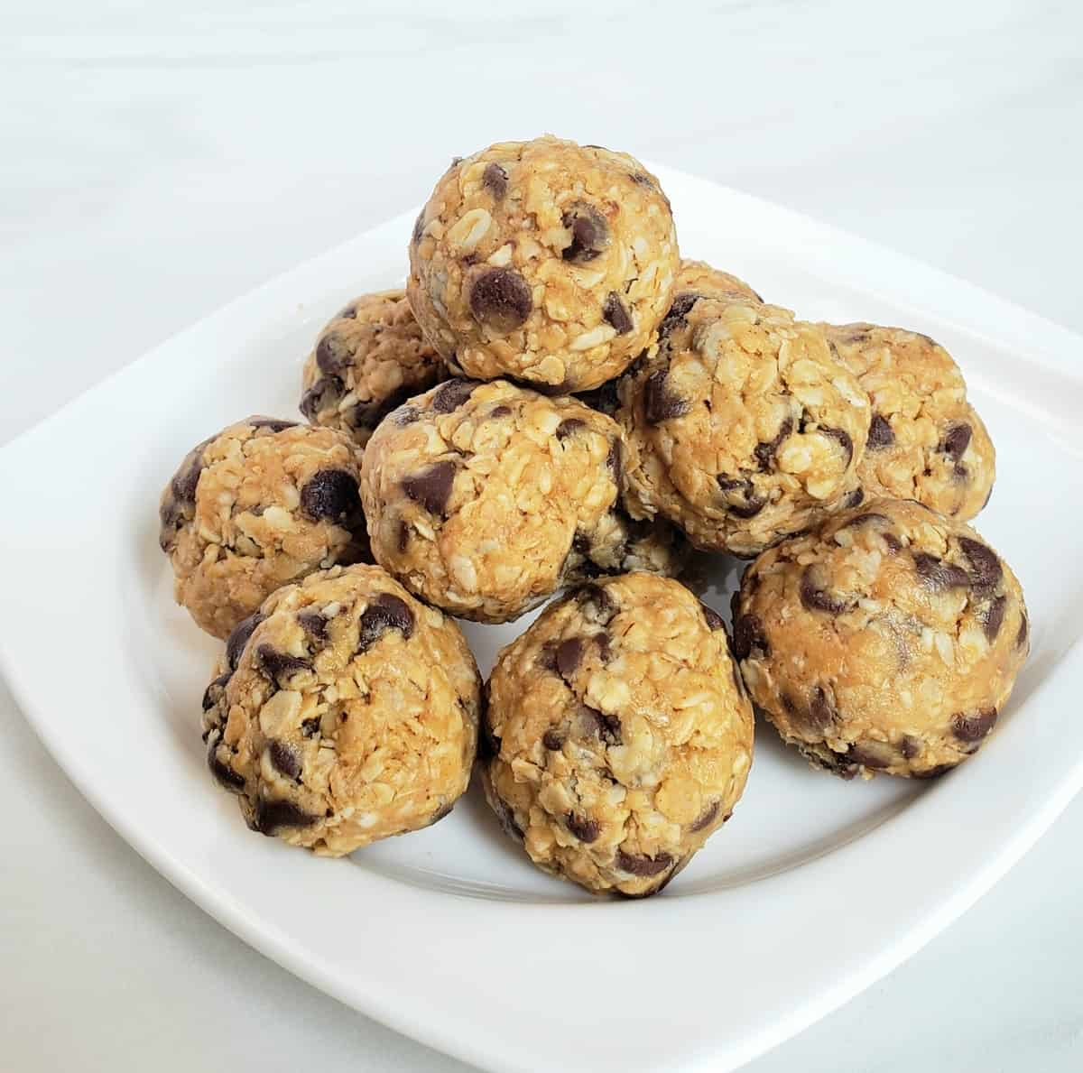 pyramid stack of peanut butter energy bites with chocolate chips on a white plate