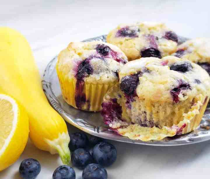 Lemon Blueberry Yellow Squash Muffins on pewter platter with squash and blueberries on surface