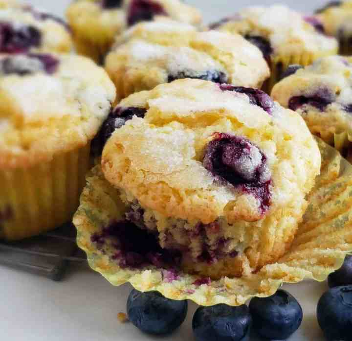 close up blueberry muffin with paper liner peeled back