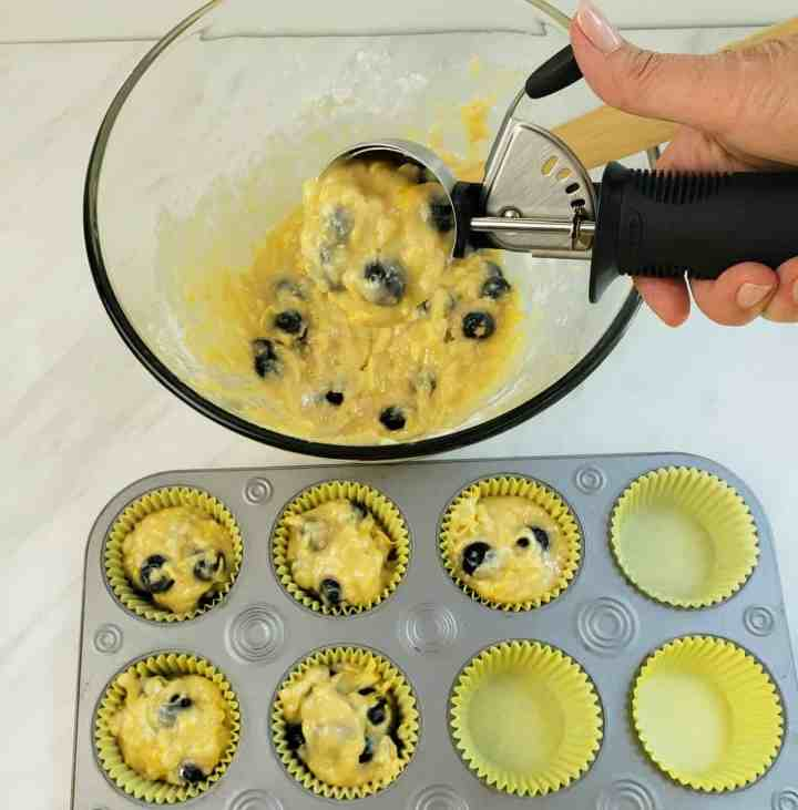 scooping lemon blueberry muffin batter in muffin cups with ice cream soop