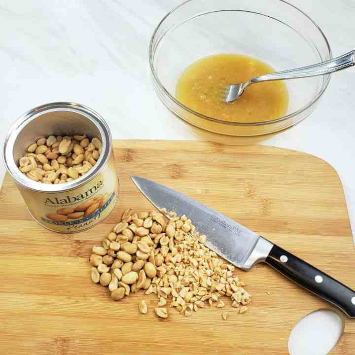 Chopped peanuts on a wooden cutting board with a chef knife; can of open peanuts