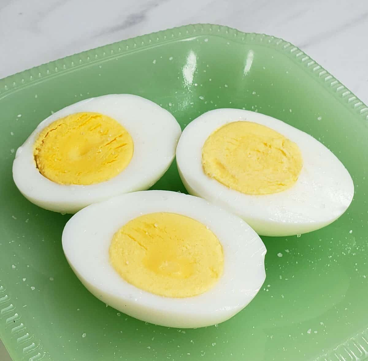 hard cooked eggs cut in half on a green plate