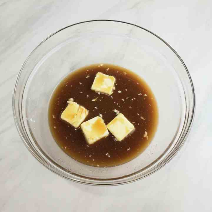 Combining butter and brown sugar and water in a glass bowl