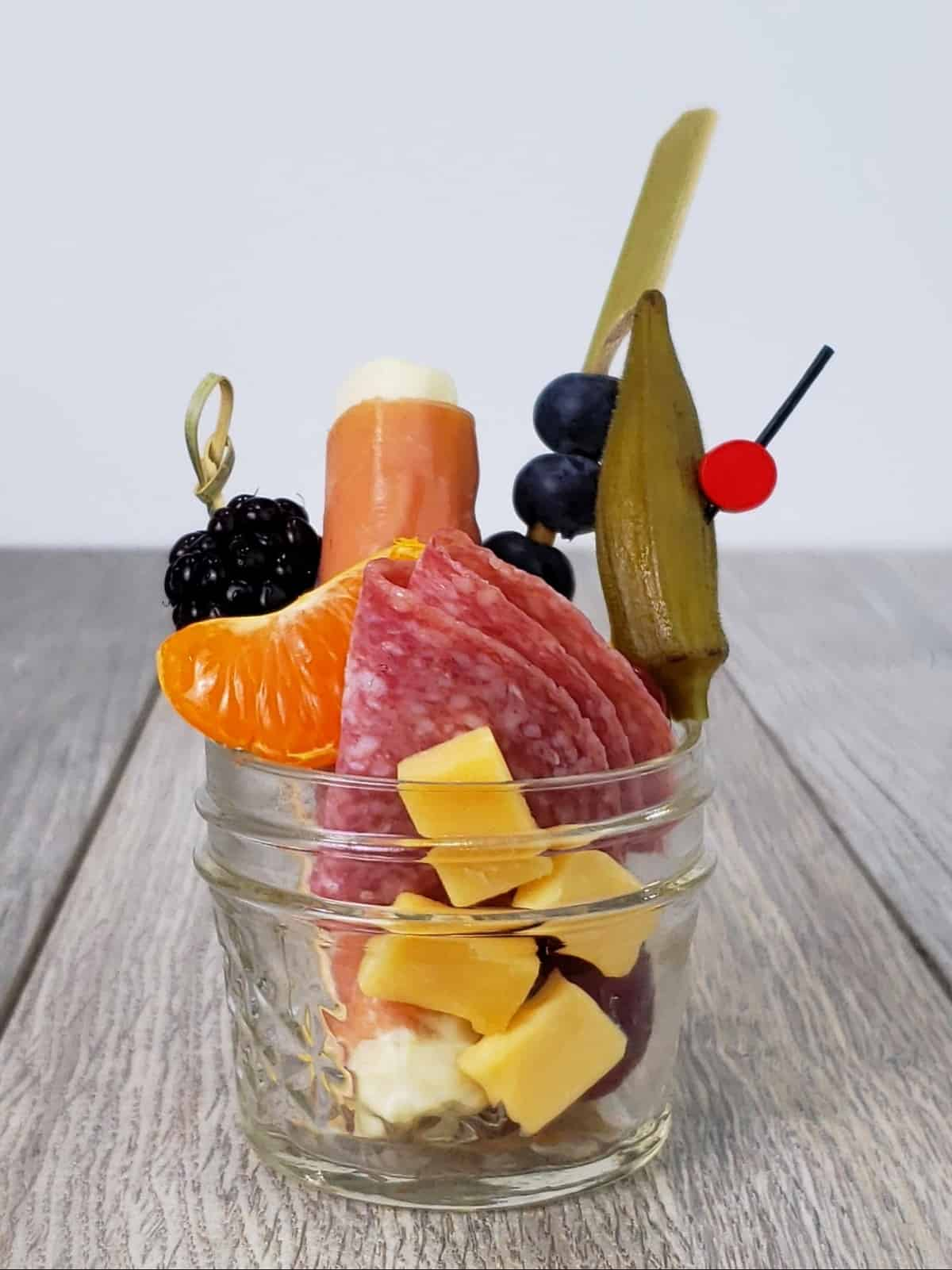 Small Mason jar filled with charcuterie snacks