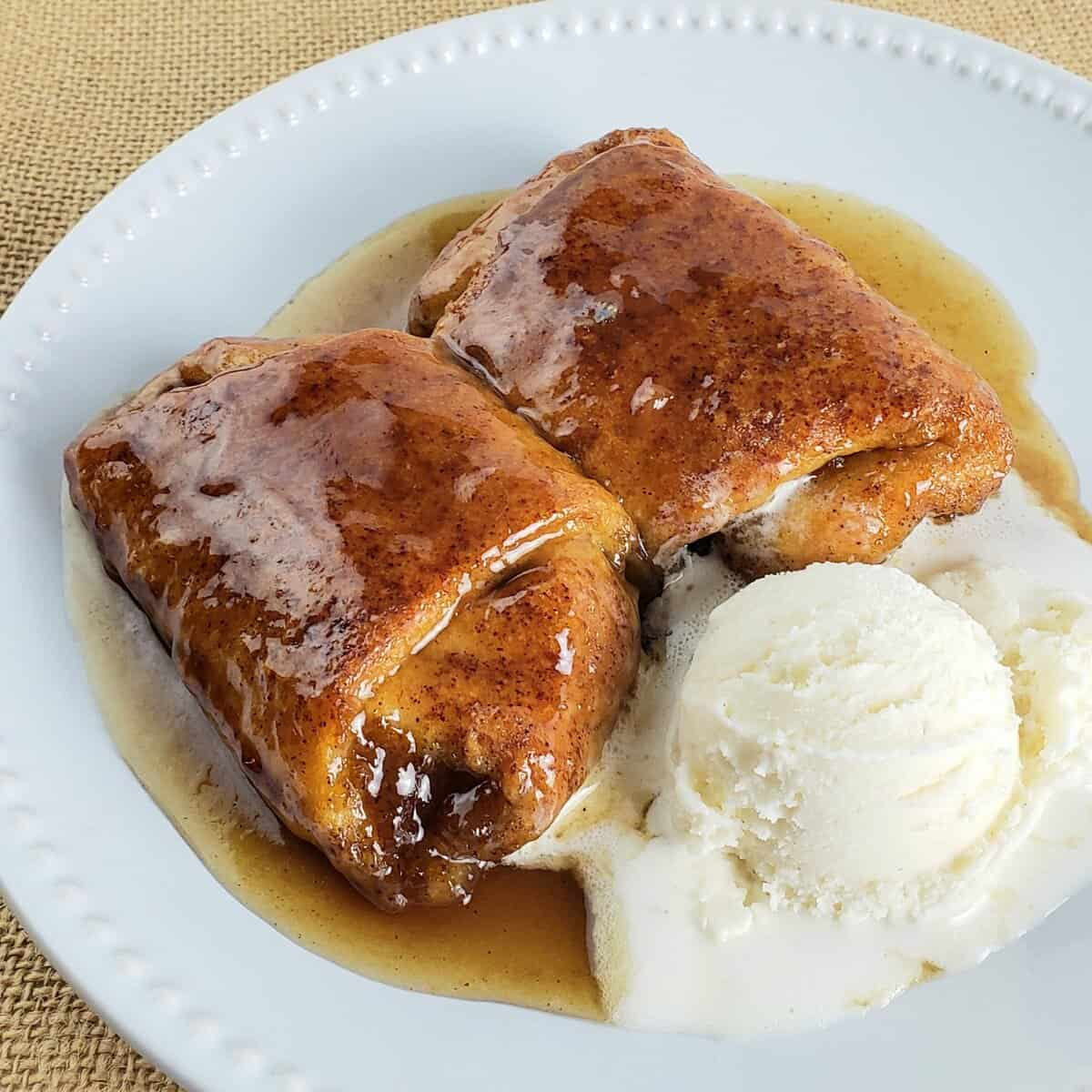crescent roll pumpkin dumplings with a scoop of ice cream on white plate
