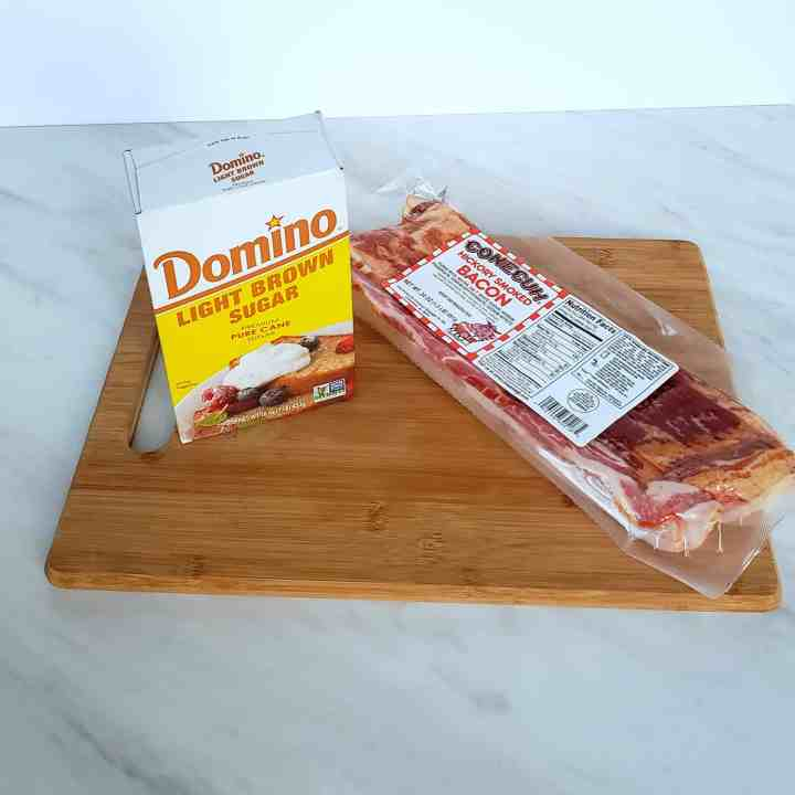 A package of bacon and a box of brown sugar on a wooden cutting board