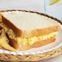 Egg salad sandwich on a paper plate and wicker charger