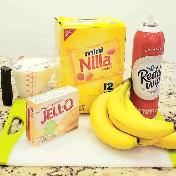 Ingredients for Walking Banana Pudding on a white cutting board: bananas, Redi whip, Nilla wafers Jello pudding milk