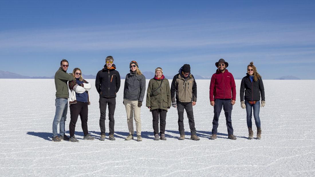 Groep mensen tijdens de jeeptocht over de Salar de Uyuni poseert op de zoutvlakte.