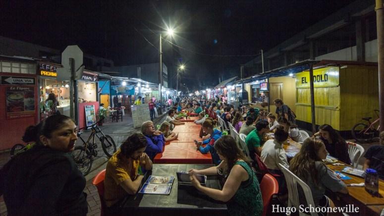 Mensen aan tafeltjes midden op straat in Puerto Ayora op het eiland Santa Cruz op de Galápagos.