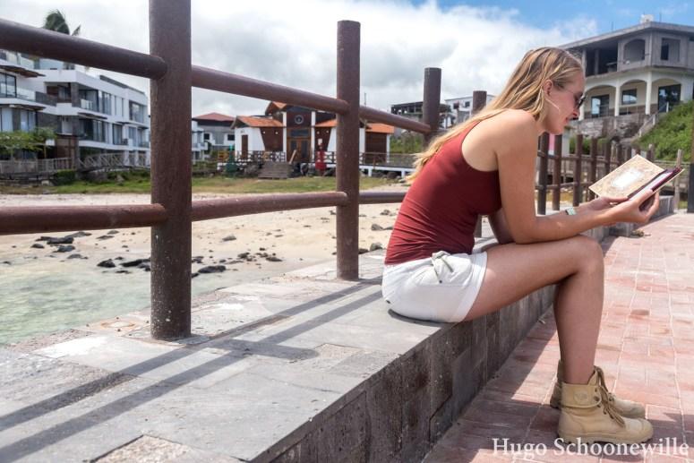 Meisje met boek in e-reader in de haven van San Critsobal op de Galapagoseilanden
