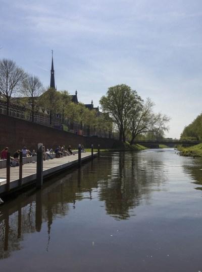 Mensen relaxen in het zonnetje langs de rivier Dommel in Den Bosch.